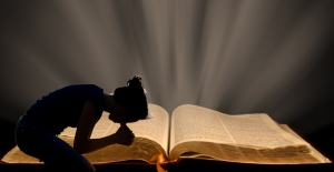 woman praying over Bible