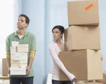 Couple moving boxes with annoyed woman